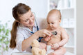 Cute woman pediatrician examining of baby kid with stethoscope women heartbeat in office Stock Image
