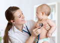Cute woman pediatrician examining of baby kid with stethoscope women in office Stock Image