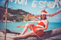 Cute woman in red dress, sunglasses and santa hat sitting on palm tree at exotic tropical beach. Holiday concept for New Royalty Free Stock Photo