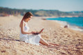 Cute woman with white laptop on the summer beach sexy and happy beautiful in a dress using Stock Images