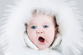Cute yawning baby girl wearing huge white fur hat Royalty Free Stock Photo