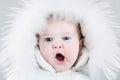Cute yawning baby girl wearing huge white fur hat Royalty Free Stock Photo