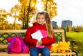 Cute years old girl after school in autumn park nice sitting on bench with backpack Royalty Free Stock Images