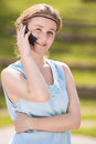 Cute young blond woman close up portrait in blue dress speaking and happy on cellphone against green lawn of summer park vertical Stock Photography