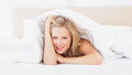 Cute young blonde smiling at camera from under the sheet home in bedroom Royalty Free Stock Photo