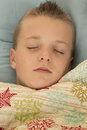 Cute young boy asleep under a snowflake blanket peace Royalty Free Stock Photo