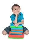 Cute young boy with books a smiling little is sitting on the floor near the pile of on the white background Stock Images