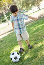 Cute Young Boy Playing with Soccer Ball Outdoors in a Park. Royalty Free Stock Photo