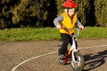 Cute young boy practising riding his bike dressed in a colourful red safety helmet and orange high visibility jacket on a quiet Royalty Free Stock Photo