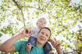 Cute young boy rides piggyback on his dads shoulders outside at the park Stock Image
