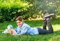 Cute, young boy in round glasses and blue shirt reads book while lying on the grass in the park. Education, back to school Royalty Free Stock Photo