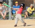 Cute young boy swinging the bat little at in a baseball game Stock Photography