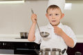 Cute young chef tasting his cooking boy in a white uniform standing with the ladle raised above the pot with a thoughtful Royalty Free Stock Image