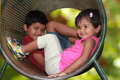 Cute young children boy girl playing in tunnel on playground the photo shows summer time with female kid smiling a Stock Photography