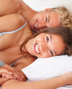 Cute young couple cuddling together in bed Royalty Free Stock Images