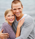 Cute young couple embracing outdoors, seaside Stock Images