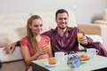 Cute young couple having breakfast, eating croissants, drinking orange juice. Royalty Free Stock Photo