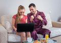 Cute young couple having breakfast, in front of laptop computer Royalty Free Stock Photo
