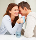 Cute young couple laughing while drinking coffee Stock Image