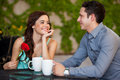Cute young couple in love beautiful girl just got a red rose from her boyfriend on a date at a cafe Royalty Free Stock Image