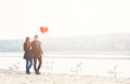 Cute young couple in love, walking at the riverside, with a red balloon Royalty Free Stock Photo