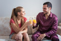 Cute young couple sitting on sofa and drinking orange juice. Royalty Free Stock Photo