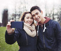 Cute young couple taking self portrait in the park looking happy while pictures using a smart phone at mixed race teenage boy and Stock Image