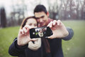 Cute young couple taking a self portrait with smartphone in park Royalty Free Stock Image