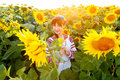 Cute young girl in embrodery on a sunflower field Royalty Free Stock Photo