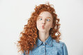 Cute young girl with foxy curly hair making funny face over white background. Copy space. Royalty Free Stock Photo