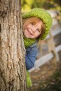 Cute Young Girl in Green Scarf and Hat Plays Peekaboo Royalty Free Stock Photo