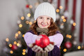 Cute young girl holding out a christmas bauble red in her hands as she stands in font of decorated tree Royalty Free Stock Photography