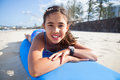 Cute young girl lying on surfboard