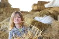 Cute young girl playing in the hay close up portrait of a at a farm Stock Image