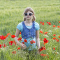 Young beautiful calm girl dreaming on a poppy field, summer outdoor