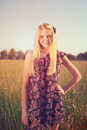 Cute young girl posing in summer field retro toned portrait of pretty blonde teenage Royalty Free Stock Photo