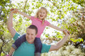 Cute young girl rides piggyback on her dads shoulders outside at the park Royalty Free Stock Photography