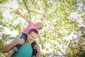 Cute young girl rides piggyback on her dads shoulders outside at the park Stock Photo