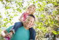 Cute young girl rides piggyback on her dads shoulders outside at the park Stock Images