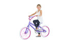 Cute young girl riding bike while posing on white background Stock Images