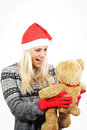 Cute young girl with santa claus hat hugging a teddy bear Royalty Free Stock Photo