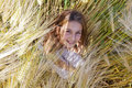 Cute young girl sitting in a barley field topview of pretty Stock Photo