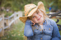 Cute young girl wearing cowboy hat posing for portrait outside smiling a Stock Image