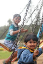 Cute young happy kids playing on swing sets in a park the photo shows summer time playground with boy and girl swinging and Royalty Free Stock Photos
