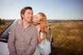 Cute young lovers are traveling by car cheerful loving couple is standing near their transport in the nature the women is Stock Photography