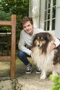 Cute young man kneeling with hairy collie dog outdoors Royalty Free Stock Photo