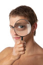 Cute young man ooking through a magnifying glass Royalty Free Stock Photo