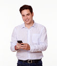 Cute young man smiling and texting portrait of a using his cellphone while looking at you on isolated studio Stock Image