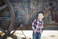 Cute young mixed race boy having fun near antique machinery outside Stock Photos