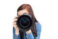 Cute young photographer taking picture of camera against white background Royalty Free Stock Images